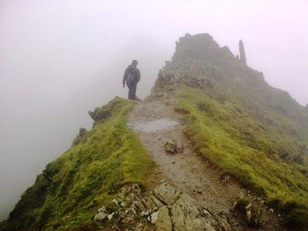 walking along the cliff edge of mount snowdon in the rain
